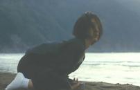 海辺で喪服でしゃがむトエ