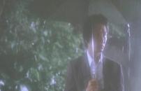 雨の中、傘をさしている男