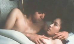 ベットでミオの乳房を揉むツギ