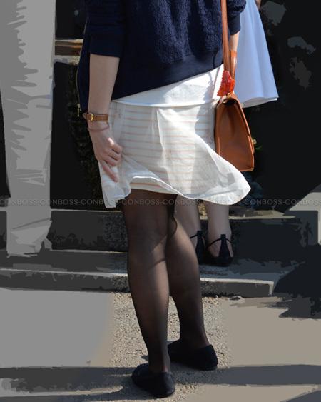 風になびくスカートと質感の良い黒タイツ